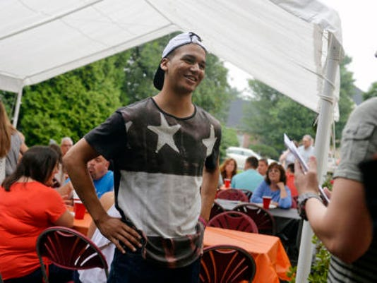 Northeastern football and basketball player Marcus Josey, center, chats with Peter Falci at Falci's graduation party in July in Manchester Township. (Chris Dunn -- GameTimePA.com)