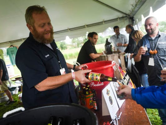 Drew Pfafflin with Penn Brewery from Pittsburgh pours samples of their seasonal Pumpkin Roll Ale during the dirst Gettysburg Brew Fest in 2014.
