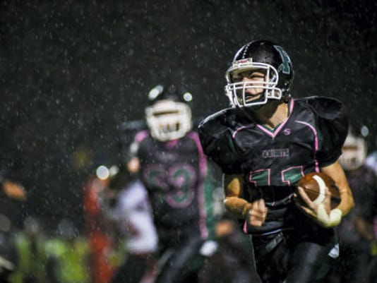 Fairfield's Michael Quealy carries the ball through the rain in the Green Knight's 2014 win over Hanover.