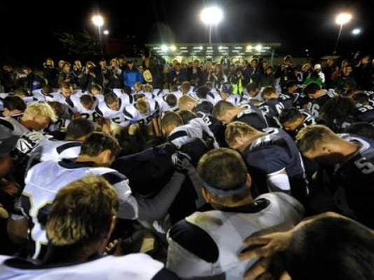 Cedar Cliff and Penn Manor players come together for a postgame prayer after the Comets topped the Colts, 27-20, in their 2014 game played in Dublin, Ireland. (JASON PLOTKIN -- GAMETIMEPA.COM)