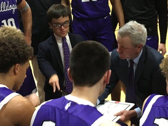 Rumson-Fair Haven basketball manager Jack Velcamp (in glasses) listens during a team huddle.