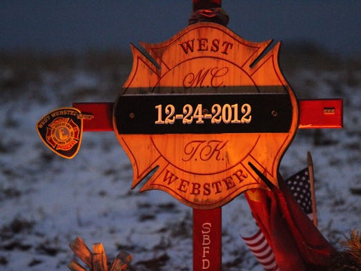 A memorial for West Webster firefighters Michael Chiapperini and Tomasz Kaczowka sits at the site on Lake Road in Webster on Dec. 24, 2013.