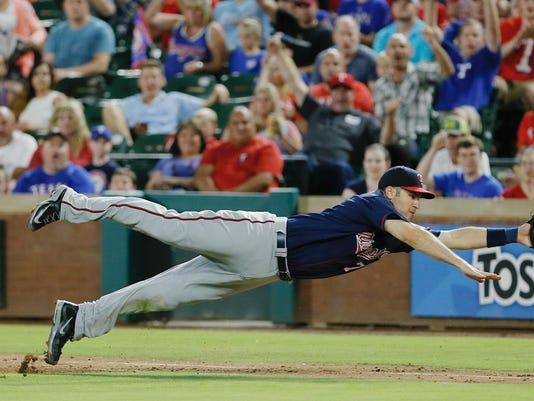 Minnesota Twins first baseman Joe Mauer dives for a wide throw from second baseman Brian Dozier during the second inning of a baseball game against the Texas Rangers on Saturday, July 9, 2016, in Arlington, Texas. Mauer was unable to make the catch and the ball went out of play. (AP Photo/Brandon Wade)