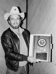 Merle Haggard poses with an award he received from the city of Redding for hosting a toy-collection concert in 1989.