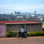 Property stands on the city skyline beyond a motorcycle taxi driver waiting for customers at a roadside in Kigali, Rwanda, on Wednesday, Sept. 18, 2013. Coffee-producing Rwanda's economy has doubled in size in the nine years through 2010, according to the World Bank.