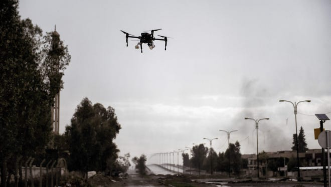 A picture taken on March 14, 2017 in the northern Iraqi city of Mosul shows a drone carrying two grenades flying in a test flight by Iraqi forces which aim to use it against Islamic State militants.