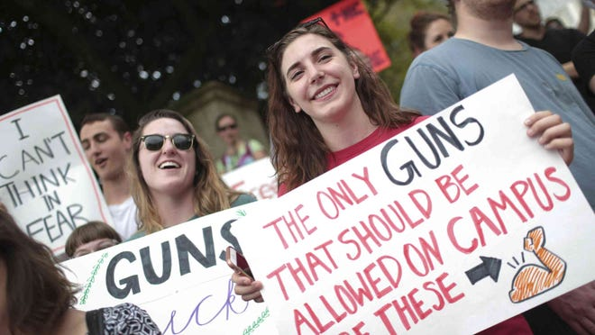 """Emily Mayville, left, and Ava Alabiso, both opponents to Georgia House Bill 280, AKA the campus carry bill, gather at the University of Georgia Arch in Athens, Ga., March 21, 2017. """"I'm worried about students walking around with guns, students are sleep deprived and stressed,"""" said Mayville. The bill applies to students 21 years and older who receive permission to have a concealed carry permit in Georgia."""