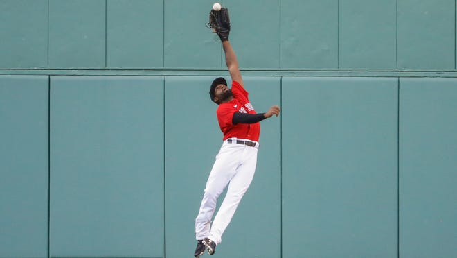 Boston Red Sox center fielder Jackie Bradley Jr. makes a leaping catch on a ball hit by Toronto Blue Jays' Rowdy Tellez during the sixth inning of the first baseball game of a doubleheader Friday, Sept. 4, 2020, at Fenway Park in Boston.