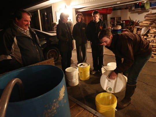 Ryan Carolfi, 16, right, of Marshfield, pours maple sap into a bucket at the home of Sam and Jenny Voight in Marshfield near Lincoln Elementary School, Thursday, March 19, 2015. The sap was brought to the Voight's home by the Wittman family, from left, Mark, Patti and Lee (center right), all Marshfield. Jenny Voight, center, talks with Patti Wittman.