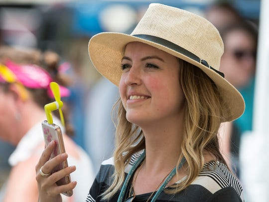 Natalie Wilson, of Toronto, Canada, utilizes a fan attached to a phone during the 2018 CMA Music Festival on Saturday, June 9, 2018, in Nashville, Tenn.