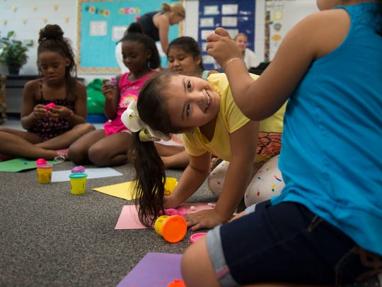 Allison Castro, 6, smiles while building animals out of Play-Doh with Yareli Duran Angel, 6, during the Franklin Special School District Summer Reading Camp at Johnson Elementary School on Tuesday, July 10, 2018, in Franklin, Tenn. After building their creations, students took time to write about their animals.
