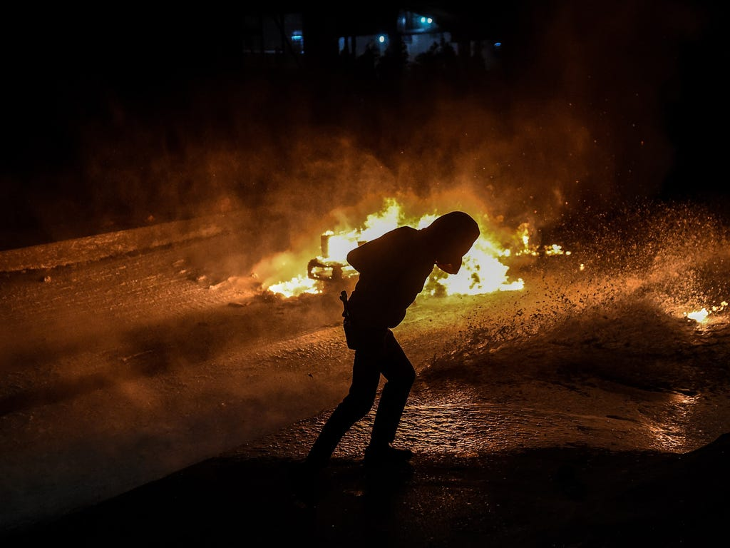 A fire burns in the background as a militant dodges water from a water cannon during a demonstration in Istanbul's Gazi district  against the deadly attacks in Ankara. Anger towards President Recep Tayyip Erdogan over Turkey's worst-ever terrorist at