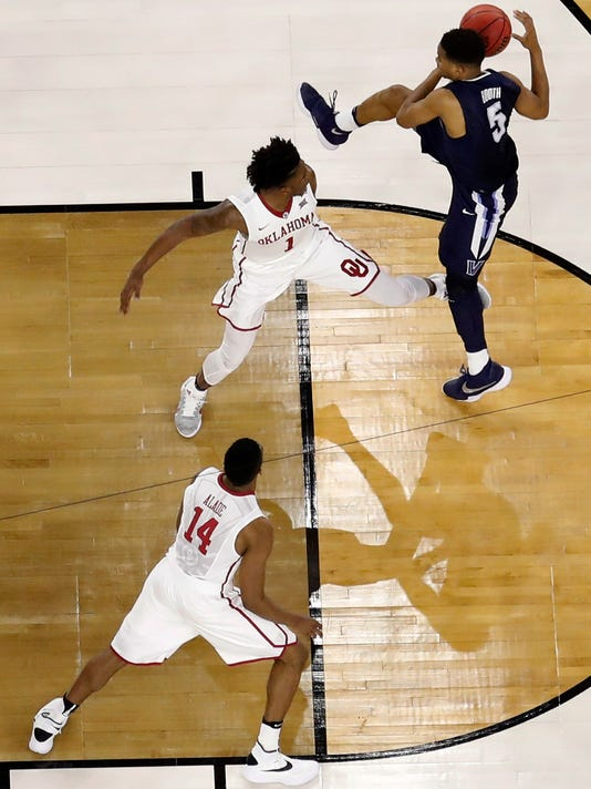 Villanova's Phil Booth (5) grabs a rebound against Oklahoma's Rashard Odomes (1) as Oklahoma's Bola Alade (14) watches during the second half of the NCAA Final Four tournament college basketball semifinal game Saturday, April 2, 2016, in Houston. (AP Photo/Carl Peer)