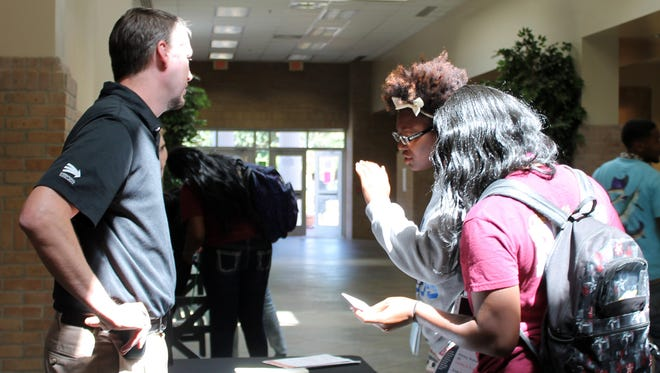 Pearl River Community College students Sharelle Singleton of Sandy Hook, left, and Ashleigh Lewis of Gulfport talk to Kohler Engines recruiter Trey Smith about temporary part-time jobs at the company in Hattiesburg.