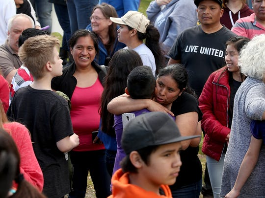 Parents embrace students Wednesday at the Theler Community Center in Belfair.