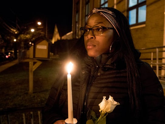 Tykeeya Mitchell of Asbury Park lights a candle. Mourners