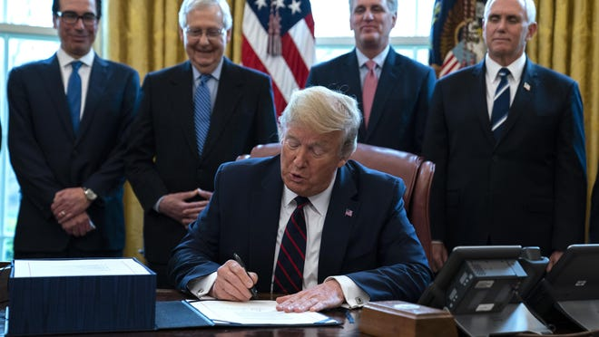 President Donald Trump signs the coronavirus stimulus relief package in the Oval Office at the White House on March 27 as Treasury Secretary Steven Mnuchin, Senate Majority Leader Mitch McConnell, R-Ky., House Minority Leader Kevin McCarty, R-Calif., and Vice President Mike Pence watch.