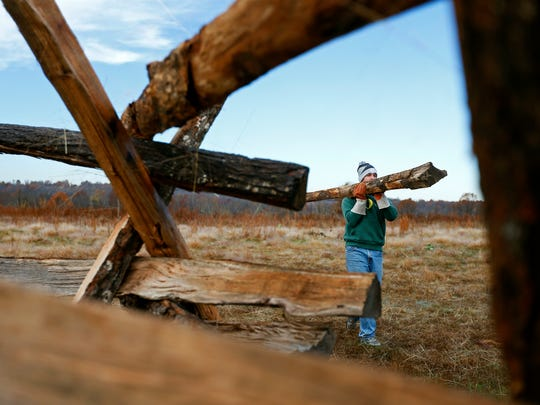 Logan Swearengin carries a log as he helps build a split rail fence as a community service project for him and his triplet brothers Ethan and Austin to earn their Eagle Scout badge. The fence is being built at the historical fence line of the Ray property at Wilson's Creek National Battlefield in Republic, Mo. on Nov. 7, 2015.