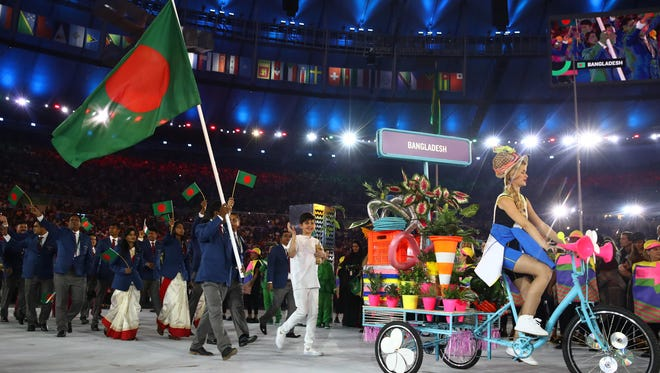 Golfer Mohammad Rahman carries the Bangladesh flag during the opening ceremony.
