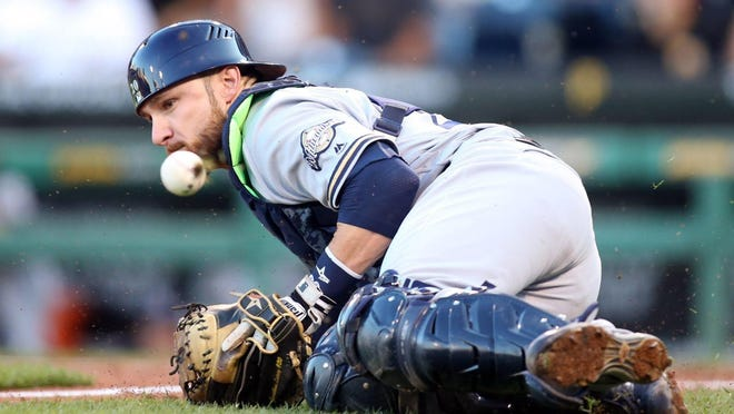 Brewers catcher Jonathan Lucroy slides to block an errant throw against the Pirates during the second inning at PNC Park.