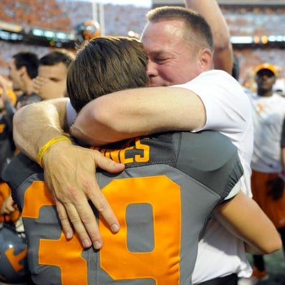 Tennessee head coach Butch Jones hugs his son Alex