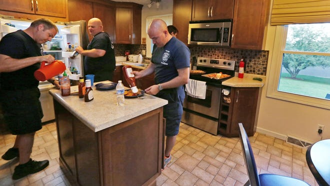 Carmel Fire Department firefighters Jeff Grimes (from left), Lt. Ian Reppert and Brad Allen get dinner in the temporary home of Station No. 44.