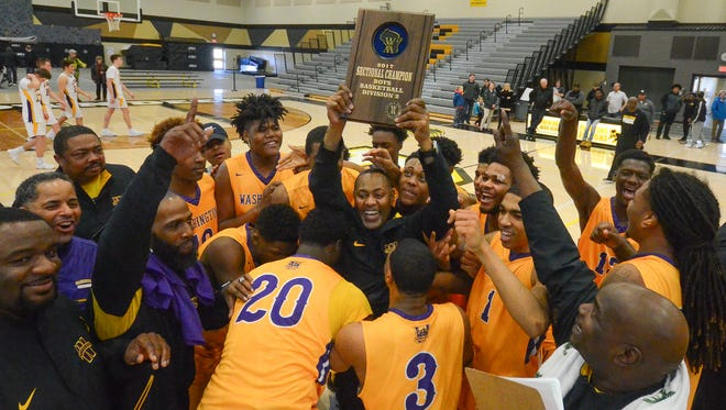 Milwaukee Washington High School basketball players swarm coach Freddie Riley as he hoists the sectional champion's plaque after the Purgolders beat New Berlin Eisenhower.