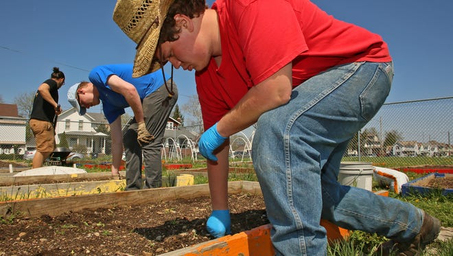 Randal Spence, forward, Joshua Coleman and Graham Judge prepare garden beds for planting Wednesday at the community garden on East Main Street at the former Lincoln Middle School property. Judge is the garden manager for Together We Grow which is non-profit Community Supported Agriculture.