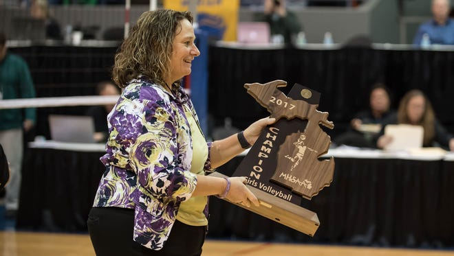 Bronson's head coach Jean LaClair hold the champion trophy for winning the MHSAA Class C Volleyball Championships three years in a row on Saturday, Nov. 18, 2017.