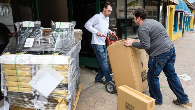 Travis Schertz and Sam Polito, co-owners of Polito's Pizza, move in a shipment of equipment and supplies Thursday, April 12, at their new St. Cloud location, 515 West St. Germain St.