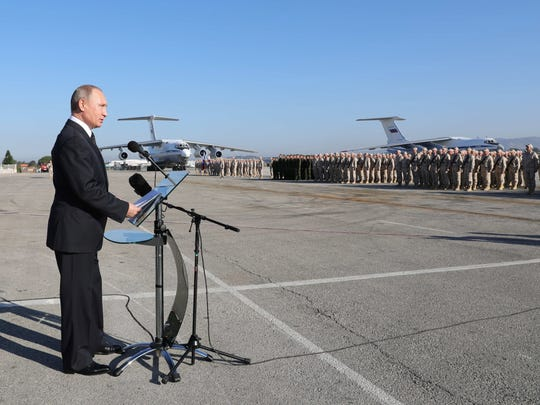 Russian President Vladimir Putin visits the Hmeimim (also Khmeimim) Air Base, south-east of the city of Latakia in Syria, with transport planes seen in the background on Dec. 11, 2017.