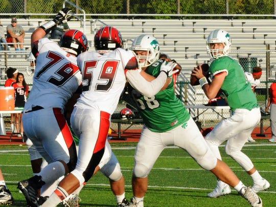 Novi quarterback Alec Bageris sets up to throw  against
