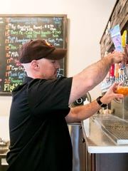 Matt Williams, the owner of Oil Well Craft Beer, pours an MIA- Neon White IPA at the Ave Maria tasting room.