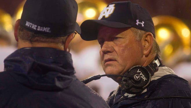 Notre Dame Fighting Irish head coach Brian Kelly, from last year's game at Clemson, played in heavy rain.