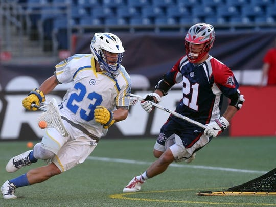 FOXBORO, MA — MAY 30: Brett Queener #23 of Florida Launch runs by Ryan Young #21 of Boston Cannons at Gillette Stadium on May 30, 2015 in Foxboro, Massachusetts. (Photo by Jim Rogash/Getty Images)