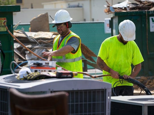 In this file photo, a demolition crew sorts recyclable materials as they help tear down a building near the corner of Fifth Avenue South and Fifth Street South on Wednesday, May 11, 2016, in Naples. Demolition work began Wednesday morning in preparation for demolition of the building to be replaced by a planned 3-story commercial and residential structure by local businessman Phil McCabe. (David Albers/Staff)