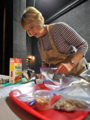Volunteer Phyllis Baumann, of Weston, measures some