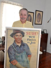 Charles Duaray holds a vintage World War I poster. His collection will be on display at FineMark Bank in Estero.