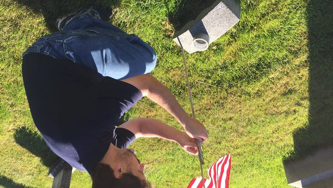 Brian Lawrence fixes a flag beside a Civil War veteran's grave marker that has sunk almost out of sight in St. Mary's Cemetery in Geneseo.