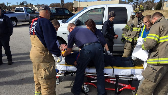 Emergency personnel treat a driver injured in a wreck Wednesday afternoon in front of Ultimate Ford on U.S. Highway 62 West.