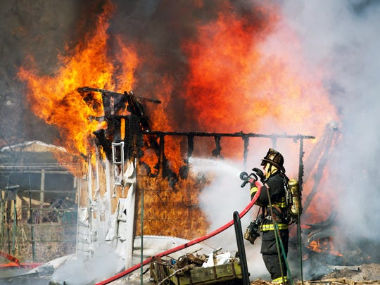 Firefighters work to extinguish a shed fire at Cedarwood and N Webster Drive in Hellam Township Mionday Feb. 25, 2013.  YORK DAILY RECORD/SUNDAY NEWS - PAUL KUEHNEL