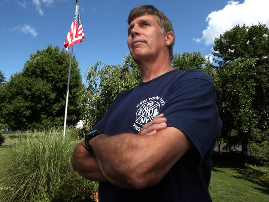 Robert Reeg stands by the flag in the front yard of his Stony Point home. The FDNY firefighter survived the South Tower collapse on Sept 11.