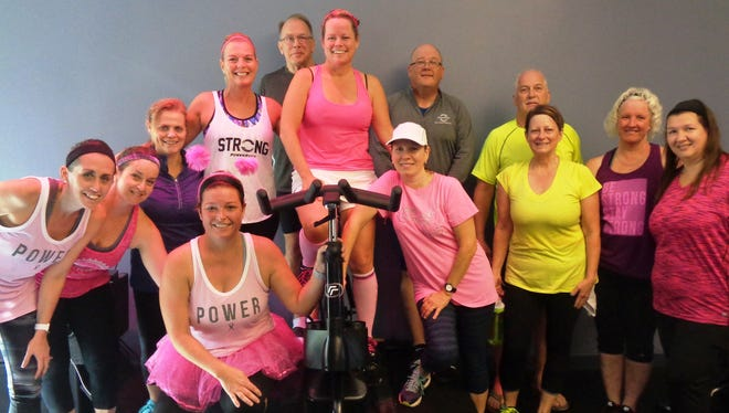 Breast cancer survivor and advocate Erin Lawry (on bike, pink top) is surrounded by her students following the Oct. 14 breast cancer fundraiser class at Power Ryde.