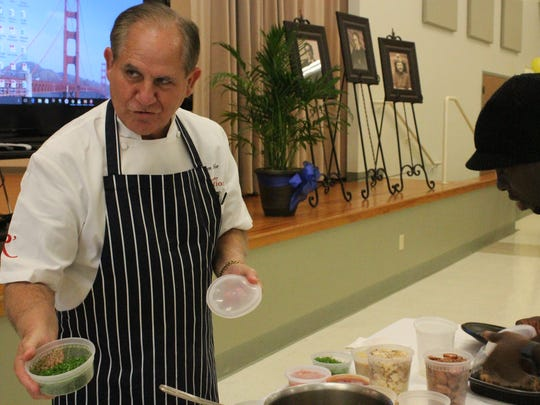 """Chef John Folse holds out a bowl of parsley. """"Parsley, always parsley,"""" he chuckled."""