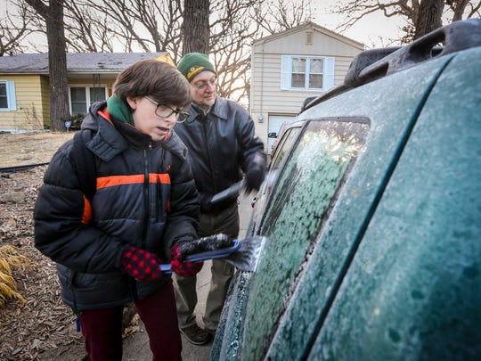 Bill Brauch and his daughter, Rachel, scrape frost off the car at their home Friday morning.