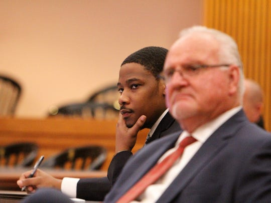 Justin Jamal Warner, left, sits for his trial on a charge of murder.