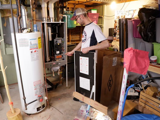 Matt Sorenson shows the damage to his furnace in his