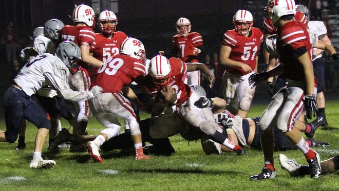 Lake Country Lutheran's Isaac Simons brings down Ismael Bastardo as part of a four-play goal line stand at the end of regulation against St. Francis on Oct. 6, preserving a 14-7 win by holding the Mariners just 3 yards shy of a potential tying score.