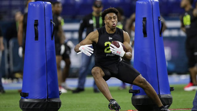 Wisconsin running back Jonathan Taylor runs a drill at the NFL football scouting combine in Indianapolis.