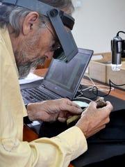 Professor John Kappelman studies Lucy's arm bone in the National Museum in Addis Ababa, Ethiopia.